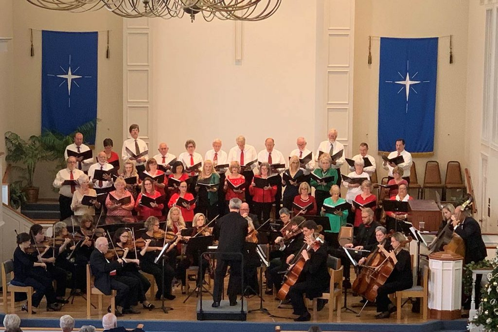 Chorus performing holiday concert in a church.