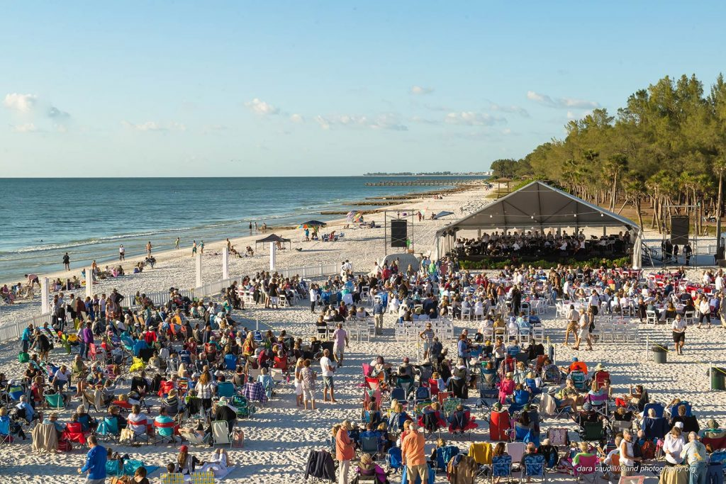 Orchestra playing to crowd on the beach.